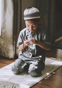 Afbeelding van moslim voorschoolse jongen bidt tot god doing dua of smeekbede concept van moslim kid bidden