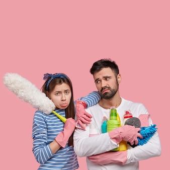 Afbeelding van neerslachtige vrouw en man die thuis schoonmaken, de voorjaarsschoonmaak doen, vermoeidheid voelen, dicht bij elkaar staan, wasmiddelen vasthouden