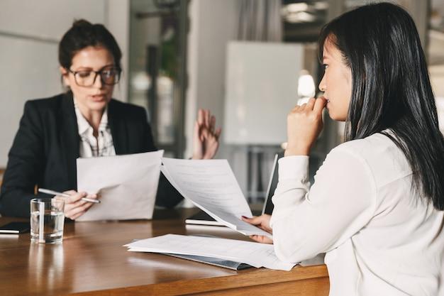 Afbeelding van nerveuze aziatische vrouw kijken en praten met zakenvrouw, zittend aan tafel in kantoor tijdens sollicitatiegesprek - business, carrière en wervingsconcept