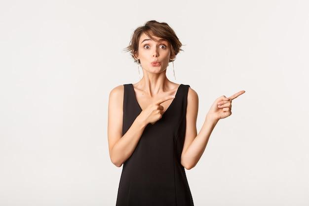 Afbeelding van nieuwsgierig meisje camera kijken en wijzende vingers recht op product, permanent over wit.