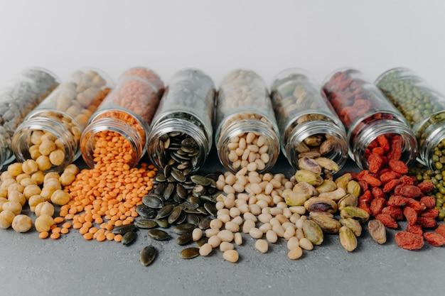 Afbeelding van nutriënten pijnboompitten, mungbonen, zonnebloempitten, kikkererwten, pistache gemorst uit glazen containers.