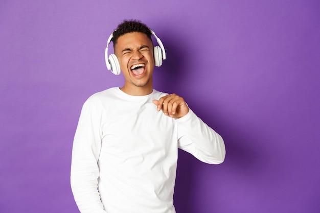 Afbeelding van onbezorgde man dansen, muziek luisteren in draadloze koptelefoons en meezingen, staande over paars.