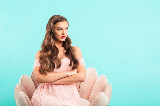 Afbeelding van ondeugende vrouw in roze jurk zittend in fauteuil met gekruiste armen en opzij kijken in wrok of belediging, geïsoleerd over blauwe muur