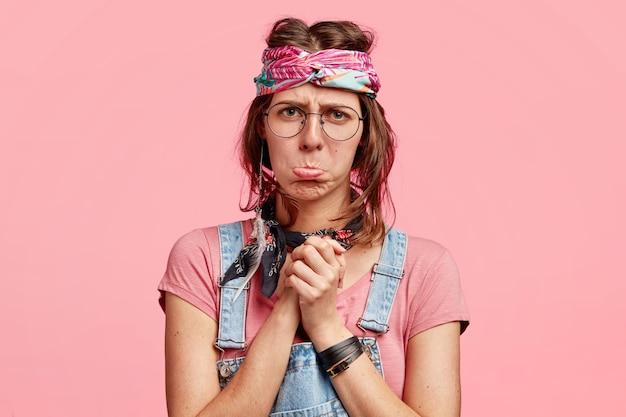 Afbeelding van ontevredenheid hippie vrouw portemonnees lippen, handen tegen elkaar gedrukt, houdt niet van iets, draagt stijlvolle outfit, behoort tot een speciale subcultuur, geïsoleerd op roze muur. negatieve emoties