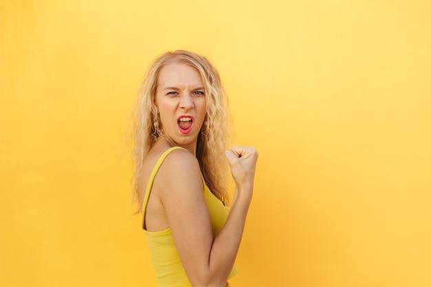 Afbeelding van opgetogen aantrekkelijke vrouw schreeuwen en winnaar gebaar maken geïsoleerd op heldere gele achtergrond