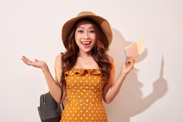 Afbeelding van opgewonden brunette vrouw 20s dragen strooien hoed terwijl paspoort met reistickets geïsoleerd over beige muur