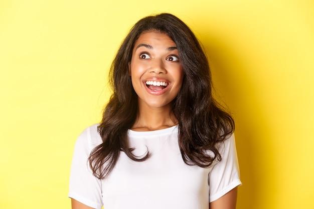 Afbeelding van opgewonden en hoopvol afro-amerikaans meisje in wit t-shirt, glimlachend en verbaasd kijkend naar advertentie in de linkerbovenhoek, staande over gele achtergrond