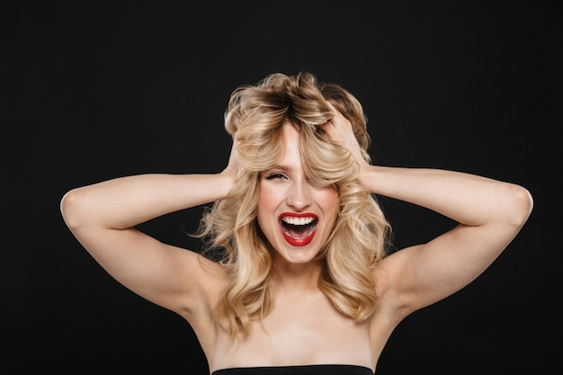 Afbeelding van opgewonden jonge mooie emotionele vrouw met heldere make-up rode lippen poseren geïsoleerd.