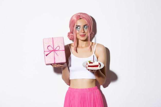 Afbeelding van opgewonden schattig meisje in roze pruik, doos met cadeau schuddend en dwalen wat erin zit, stuk verjaardagstaart vasthouden, b-day vieren