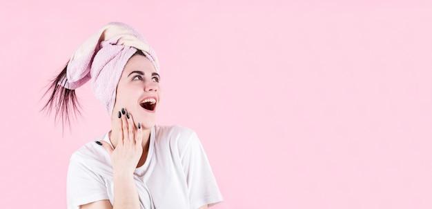 Afbeelding van opgewonden schreeuwende jonge vrouw geïsoleerd op roze achtergrond. kijkend in de rechterbovenhoek.