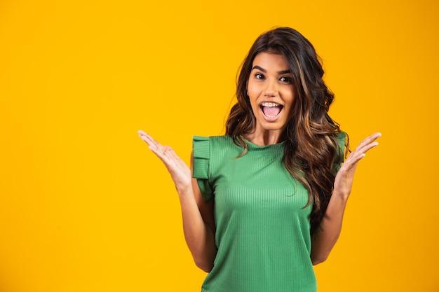 Afbeelding van opgewonden schreeuwende jonge vrouw geïsoleerd over gele achtergrond. camera kijken.