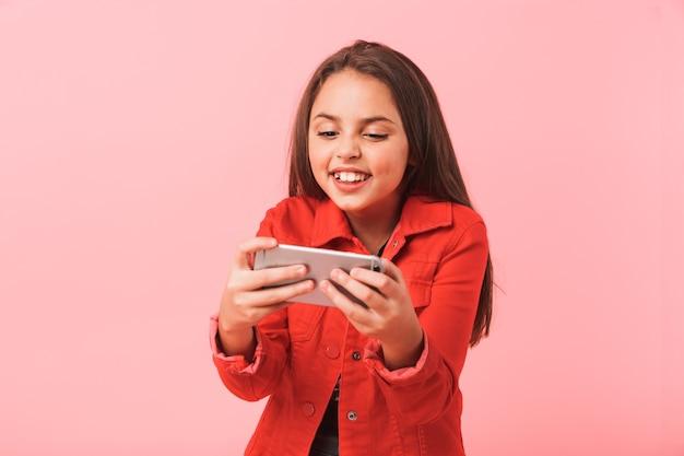 Afbeelding van opgewonden tienermeisje in casual spelen van videogames op mobiele telefoon terwijl staande, geïsoleerd over rode muur