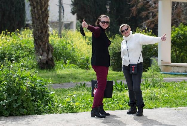 Afbeelding van opgewonden volwassen twee vrouwen die duimen opdagen terwijl ze op straat in de stad poseren. glimlacht vrolijk