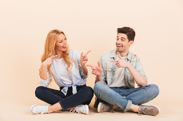 Afbeelding van optimistische vrienden man en vrouw 20s in denim kleding zittend op de vloer met gekruiste benen en wijzende vingers naar elkaar, geïsoleerd over beige muur