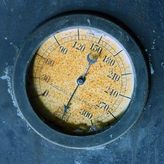 Afbeelding van oude gele meter in een metalen wand