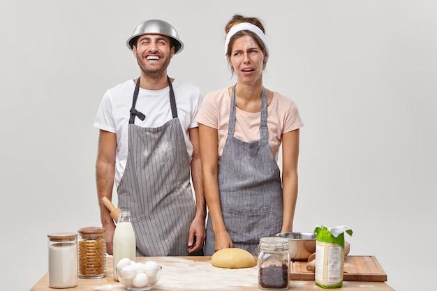 Afbeelding van overwerkte huisvrouw heeft een ongelukkige uitdrukking, man staat in de buurt, helpt met taart bakken, deeg maken, bezig met het bereiden van dessert, in keuken staan, omringd met ingrediënten of producten