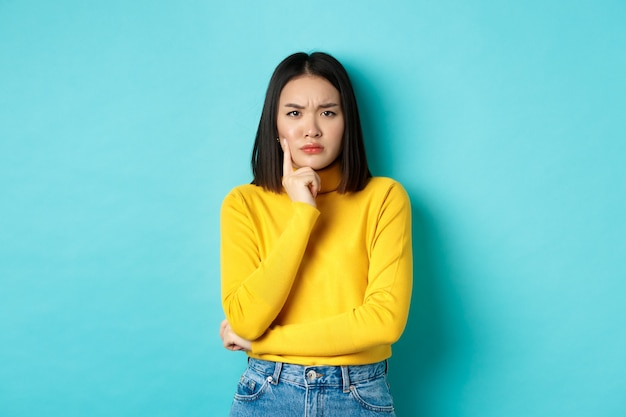 Afbeelding van peinzende en serieuze aziatische vrouw kin aanraken, fronsen en staren camera verbaasd, moeilijke keuze maken, staande over blauwe achtergrond.