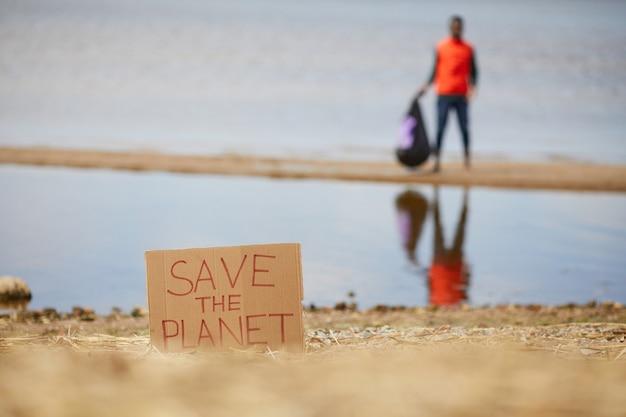 Afbeelding van plakkaat save the planet op het strand van de zee met staande man