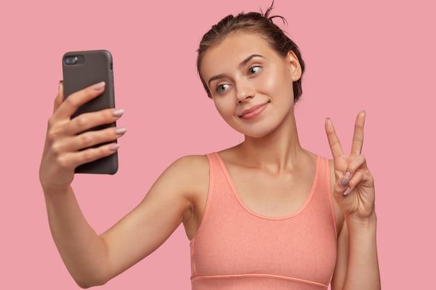 Afbeelding van positieve blanke dame met frisse huid, houdt moderne slimme telefoon vooraan, maakt vredesteken, kantelt hoofd, gekleed in casual vestmodellen over roze muur. mooi meisje neemt selfie-portret