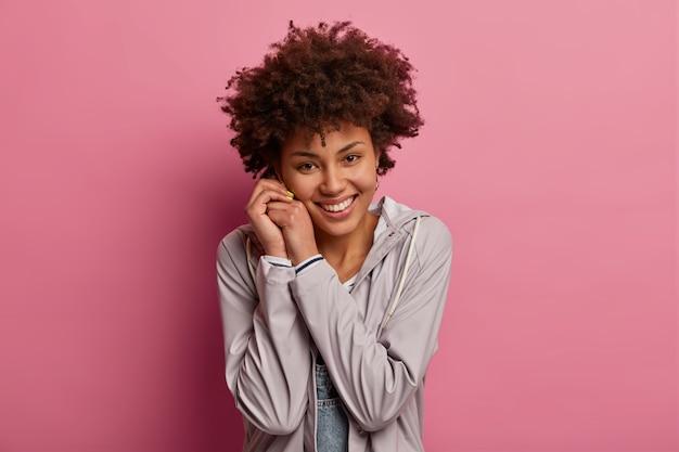 Afbeelding van positieve charmante duizendjarige meisje houdt handen bij elkaar in de buurt van gezicht, kijkt met tedere uitdrukking, hoort iets aangenaams, poseert over roze muur. positieve gevoelens concept