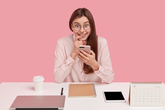 Afbeelding van positieve vrouw met vreugdevolle expressie, vinger in de buurt van de lippen houdt, cellulair vasthoudt, heeft koffiepauze, berichten in sociale netwerken