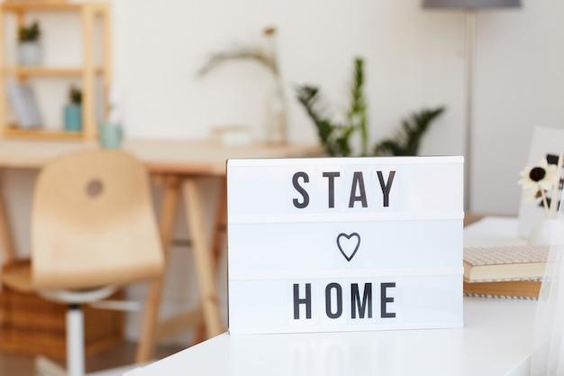 Afbeelding van poster met tekst blijf thuis op de tafel in de kamer