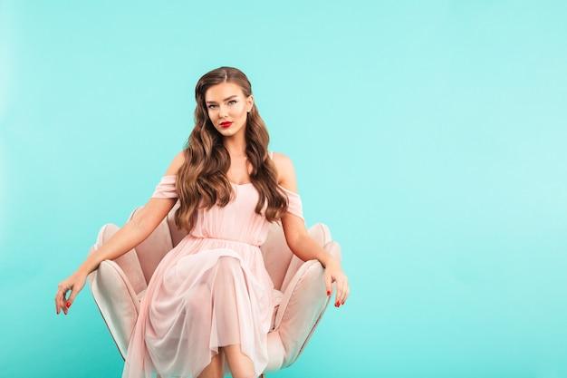 Afbeelding van prachtige vrouw 20s in roze jurk zittend in zachte fauteuil met gekruiste benen