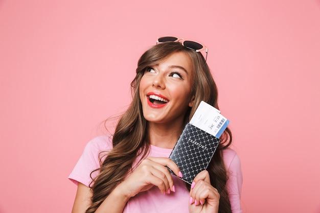 Afbeelding van reismeisje 20s met mooie bruine lokken naar boven kijkend naar copyspace terwijl ze paspoort en vliegtickets vasthoudt, geïsoleerd op roze achtergrond