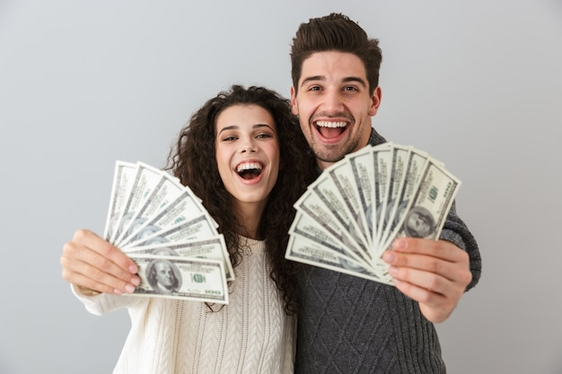 Afbeelding van rijke man en vrouw met fan van dollargeld, geïsoleerd over grijze muur