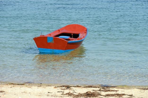 Afbeelding van rode houten vissersboot afgemeerd aan de kust