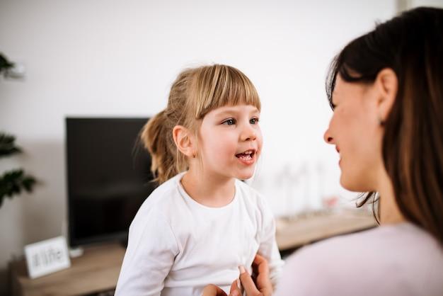 Afbeelding van schattig klein meisje in gesprek met haar moeder.
