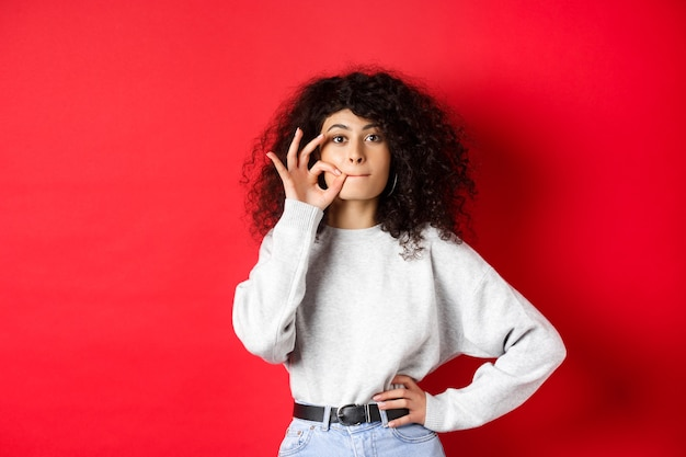 Afbeelding van schattig meisje met krullend haar dat belooft stil te blijven, lippen dicht te ritsen, zegel te maken, een geheim te verbergen, stom op rode achtergrond te staan