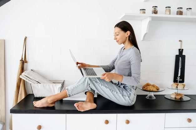 Afbeelding van schattige brunette vrouw zittend op de tafel in de keuken en het gebruik van laptop
