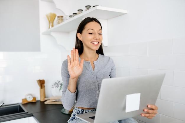 Afbeelding van schattige brunette vrouw zittend op de tafel in de keuken en met behulp van laptop