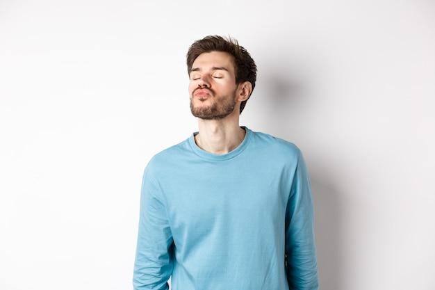 Afbeelding van schattige en dwaze man wachten op kus, tuit lippen met gesloten ogen, staande op een witte achtergrond.