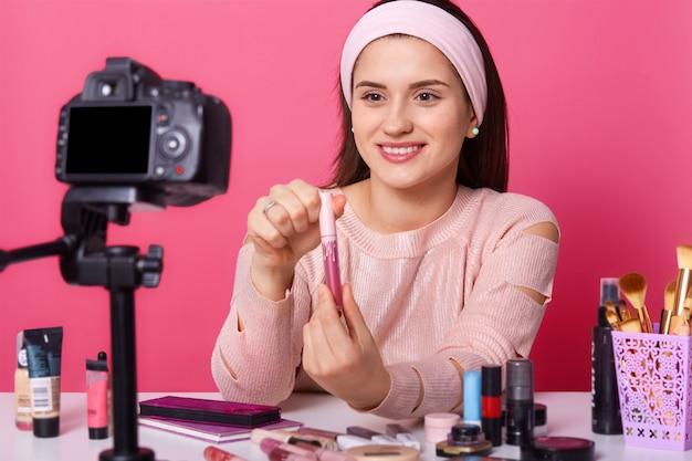 Afbeelding van schattige jonge vrouw test enkele schoonheidsproducten en toont lipgloss aan haar volgers in blog