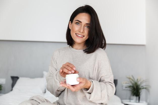 Afbeelding van schattige vrouw 30s pot met gezichtscrème, in moderne lichte kamer