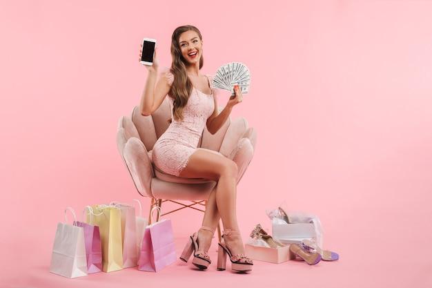 Afbeelding van schattige vrouw smartphone en geld contant te demonstreren zittend in een stoel in de buurt van boodschappentassen en schoenen dozen, geïsoleerd over roze muur