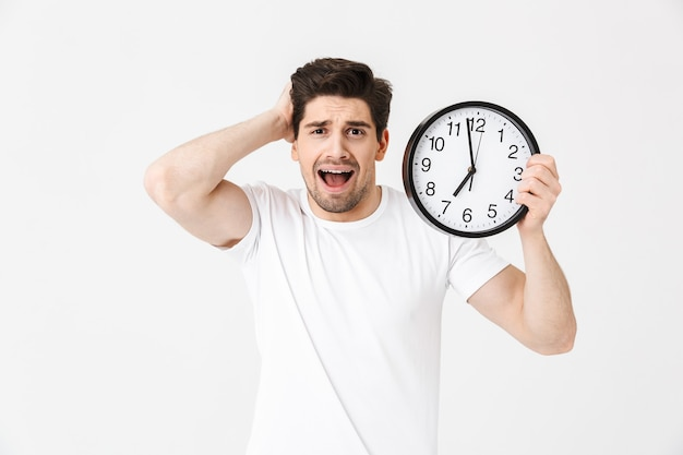 Afbeelding van schreeuwende verwarde jonge man poseren geïsoleerd over witte muur met klok.