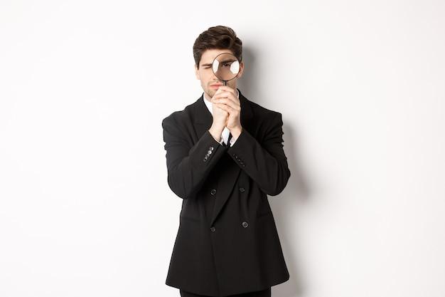 Afbeelding van serieuze zakenman in zwart trendy pak, kijkend door vergrootglas, op zoek naar werknemers, staande tegen een witte achtergrond.