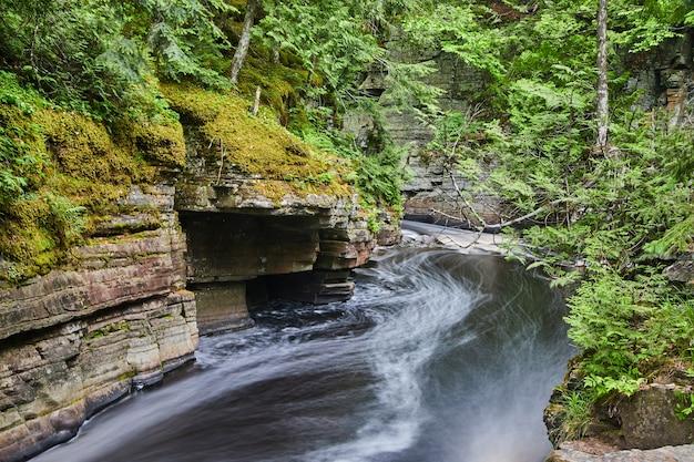 Afbeelding van snel bewegende rivier in prachtige kloof met lagen mos en stukjes korstmos in weelderig groen bos