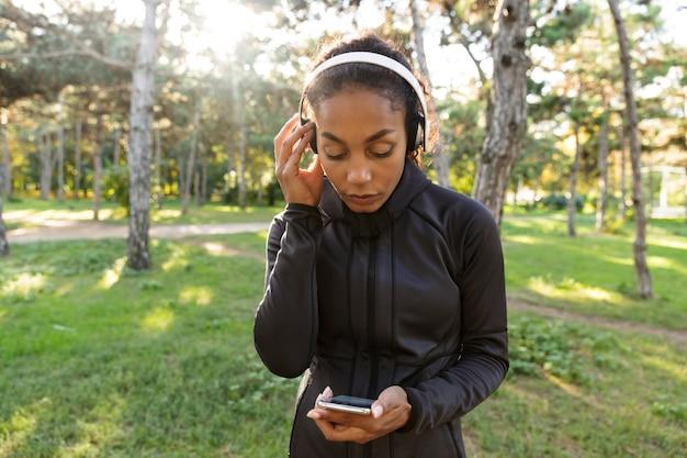 Afbeelding van sportieve vrouw 20s dragen zwarte trainingspak en koptelefoon, met behulp van mobiele telefoon tijdens het wandelen door groen park