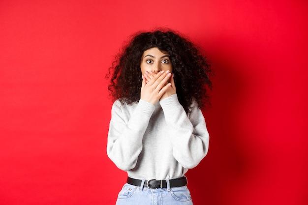 Afbeelding van sprakeloze blanke vrouw die de mond bedekt met handen, geschokt naar de camera kijkt, in vrijetijdskleding op rode achtergrond staat.