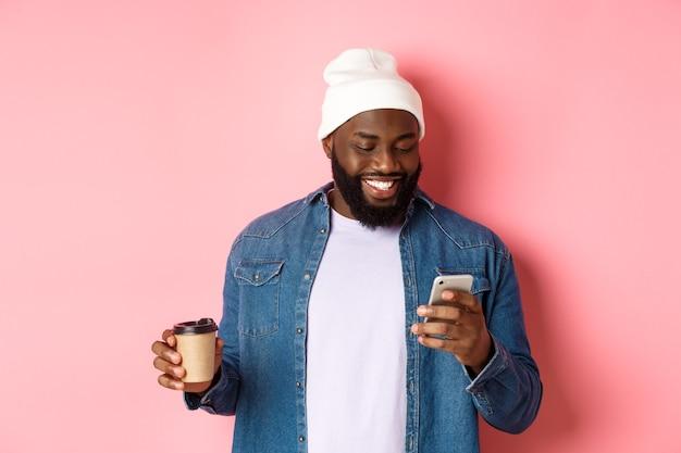 Afbeelding van stijlvolle zwarte man hipster die afhaalkoffie drinkt, bericht op telefoon leest en glimlacht, staande over roze achtergrond.