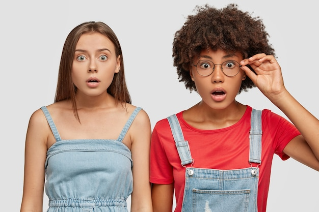 Afbeelding van stomverbaasd gemengd ras meisje staren camera met afgeluisterde ogen