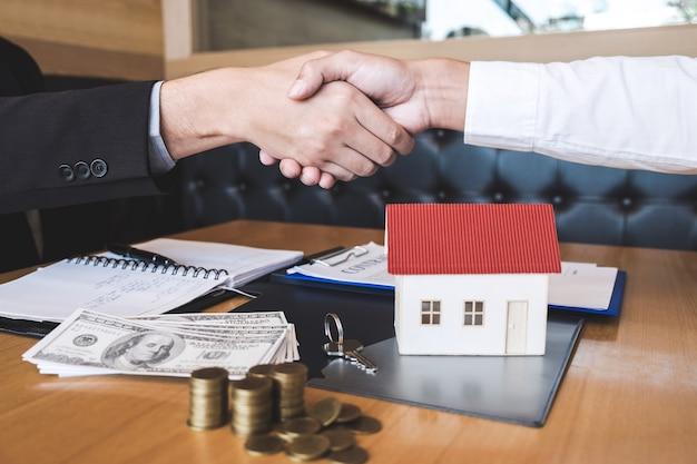 Afbeelding van succesvolle deal, makelaar en klant handen schudden na ondertekening contract goedgekeurd