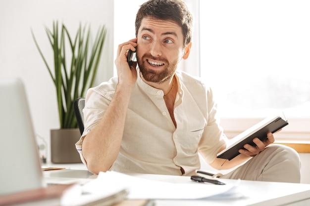 Afbeelding van succesvolle kantoormedewerker 30s dragen wit overhemd met behulp van smartphone en laptop, zittend aan tafel op de moderne werkplek