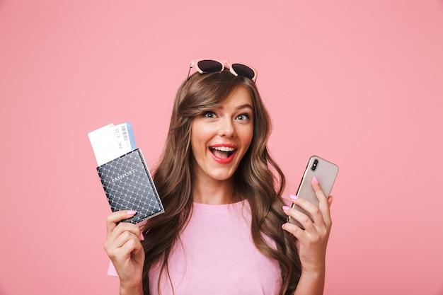 Afbeelding van succesvolle reis meisje 20s vreugde uitdrukken terwijl paspoort met vliegtickets en smartphone in handen, geïsoleerd op roze achtergrond