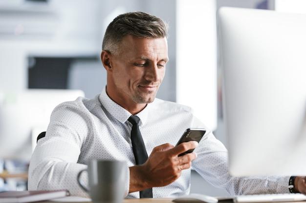 Afbeelding van succesvolle zakenman 30s dragen witte overhemd en stropdas zitten aan de balie in kantoor door computer, en mobiele telefoon te houden