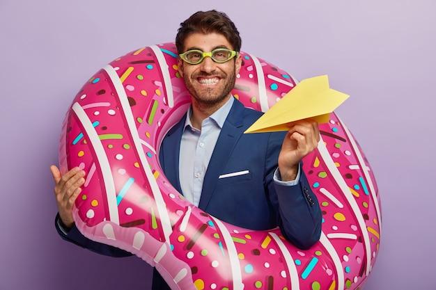 Afbeelding van tevreden europese mannelijke regisseur heeft brede glimlach, draagt handgemaakt vliegtuig